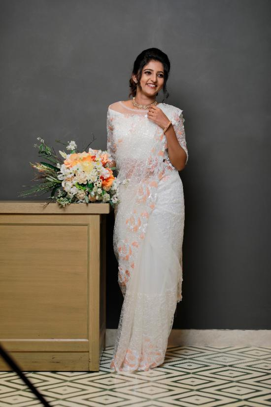 Fully embroidered pearl white net saree with peach cutbead along handwork border